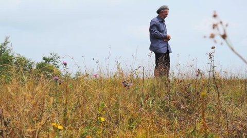 Elderly man praying on a hill. Summer day. Profile view. Still camera