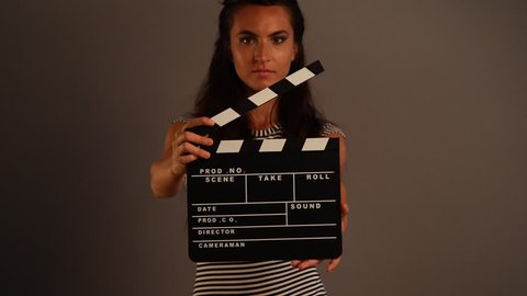 Woman portrait holding movie clapper against grey background.