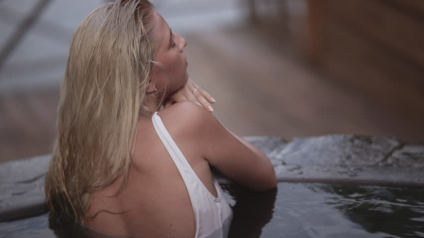 Sensual girl relaxing in outdoor spa hot pool in slow motion. Beautiful woman resting in bathtub outdoors. Female taking bath outside. Sexy woman taking relaxing bath. Sensual woman in hot pool