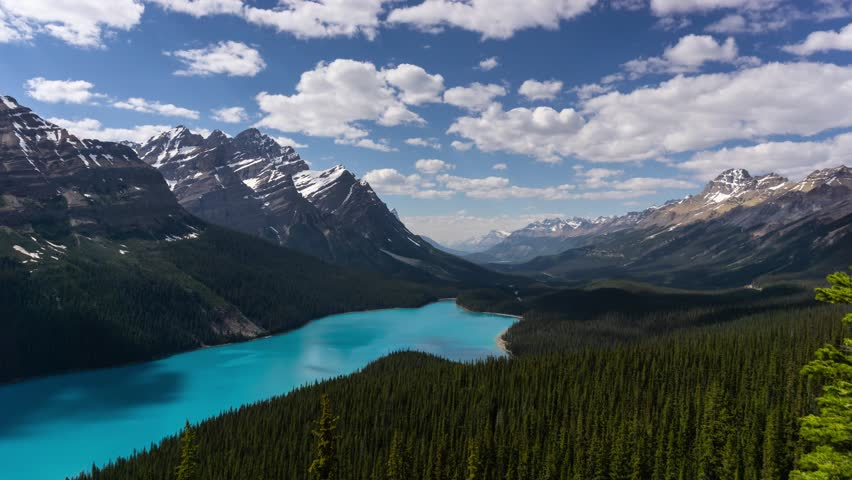 Beautiful aerial timelapse of a glacier lake in the Canadian Rocky Mountain Landscape during a vibrant cloudy summer day. Taken in Peyto Lake, Banff National Park, Alberta, Canada.