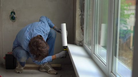 Slowmotion shot of a young man installing windowsills of a plastic window. Installer fills the seams with foam
