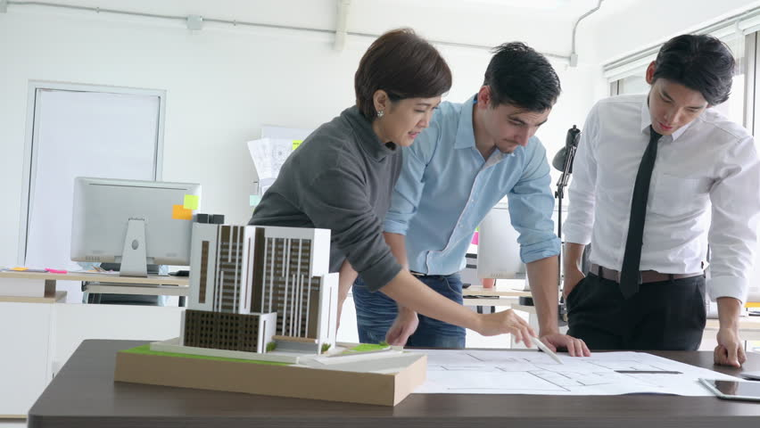 Architects team are working on paper blueprint and building model. Business woman suggest idea to designer. concept of construction, architecture, development and creative. | Shutterstock HD Video #1016959756