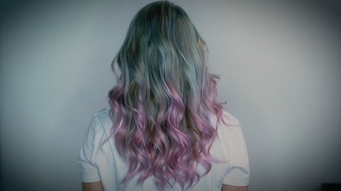 Girl with long platinum, blue and pink unicorn hair style from the back gently shaking her head.