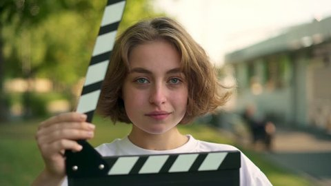 Serious young woman with short thick hair looking at camera. She is using clapperboard and starts smiling widely after that. Concept of filmmaking and acting. Slider slow motion portrait shot