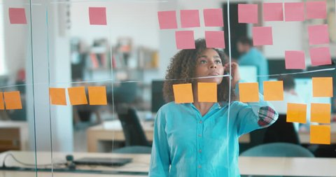 African American black employee looking onto a glass wall with sticky notes, framework for managing work, scrum methodology. 4K UHD 60 FPS SLOW MOTION