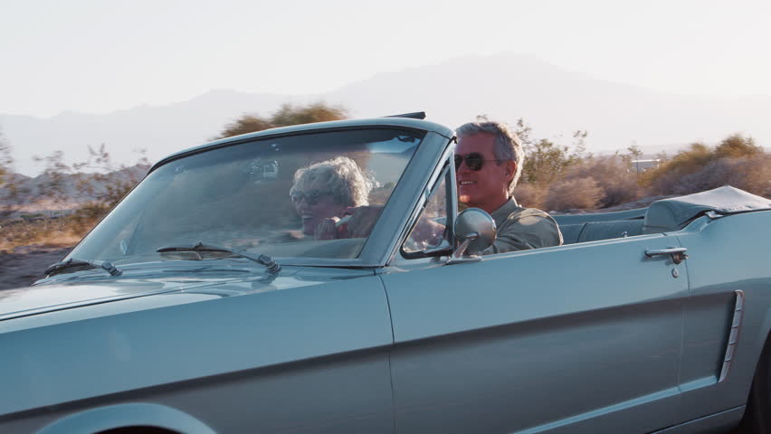 Senior white couple driving classic convertible on highway | Shutterstock HD Video #1017037456
