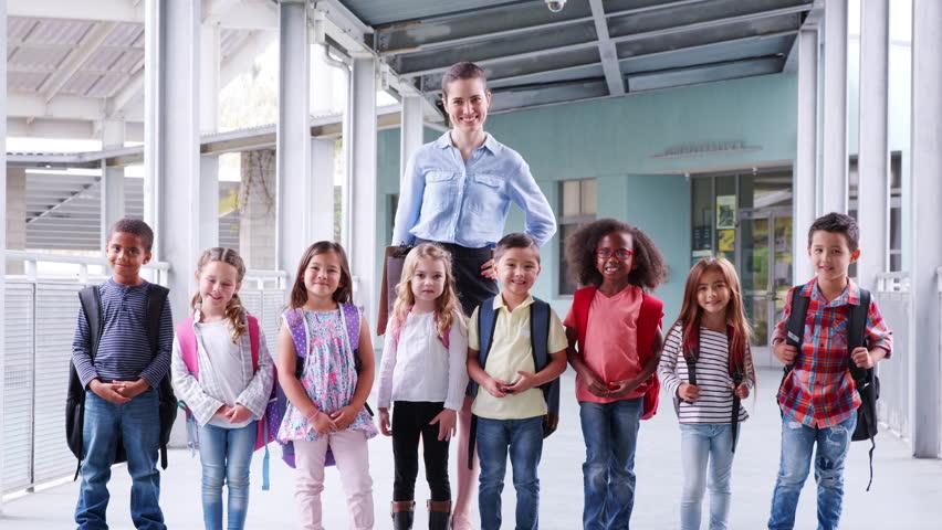 Elementary school teacher and her pupils in school corridor   Shutterstock HD Video #1017044986