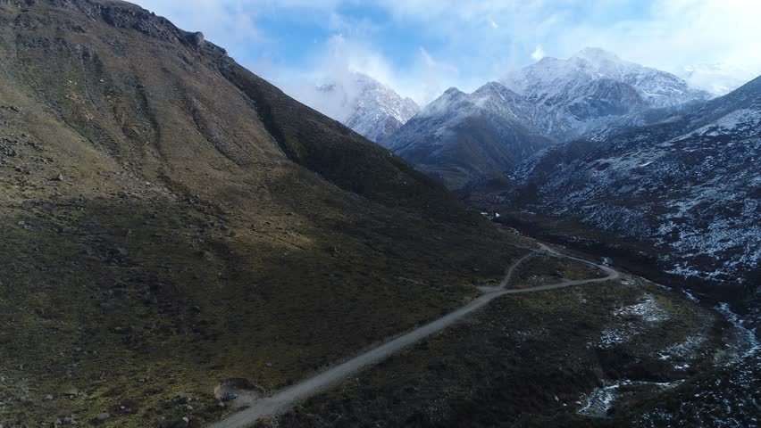 Aerial drone scene of Tunuyan valley. Snowy hill sides and The Andes Mountains at background. Clouds and blue sky, mistic landscape. Camera moving backwards. Mendoza, Argentina