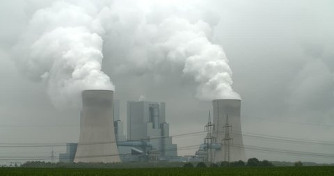 RWE power plant working on lignite producing electricity and huge clouds of steam and CO2 in Neurath, Germany, 4K