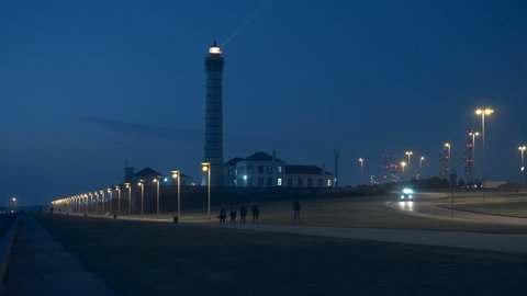 Lighthouse at early night. Group of fitness people walking, cars and refinery at background. Boa Nova lighthouse, LeÇa da Palmeira, Portugal