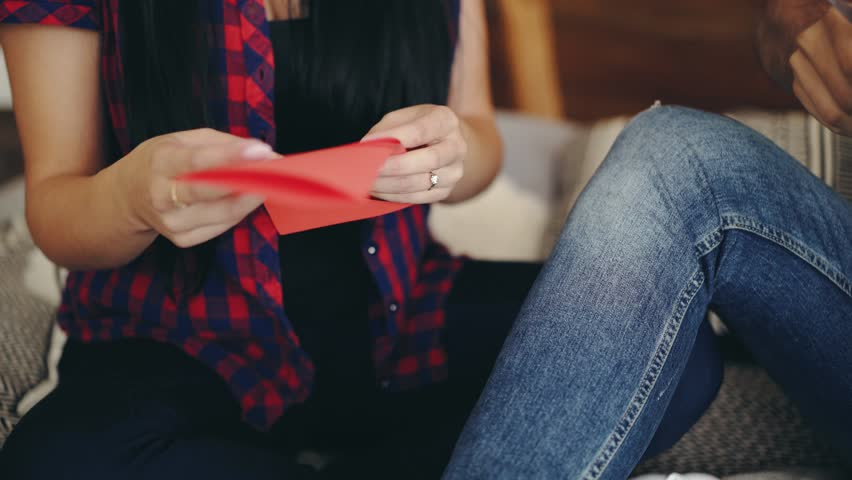 girl is showing ready carved heart from colored paper for Valentine's Day