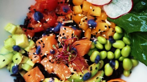 Delicious fresh vegetable salad with salmon, avocado slice, green beans & black rice served in Asian cafe.Exotic cuisine in restaurant.Healthy balanced food footage