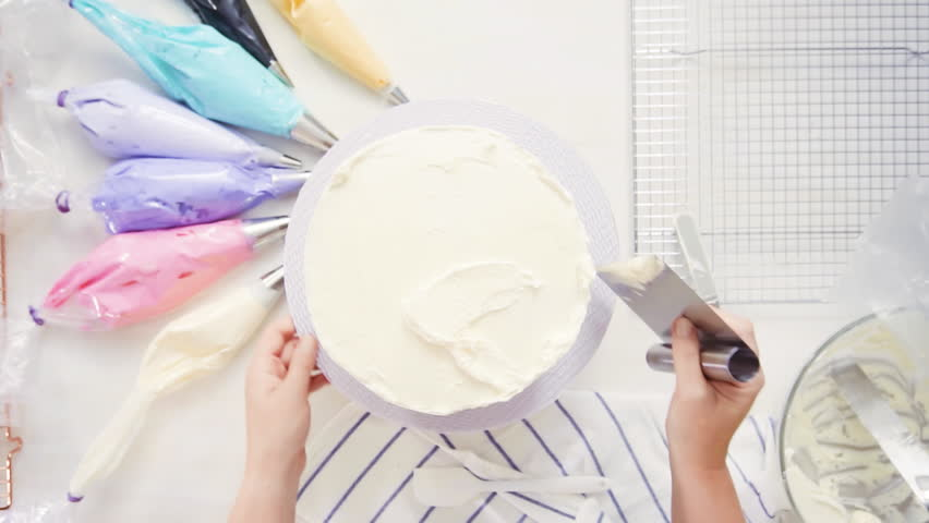 Step by step. Top view. Pastry chef stacking cake layers with buttercream frosting between to create unicorn cake. | Shutterstock HD Video #1017193276