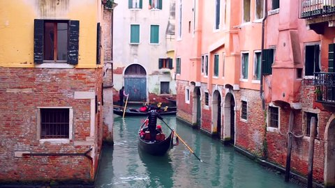 Gondoliers lined up in single line navigating the gondolas with tourists through the narrow canal in Venice Italy during winter