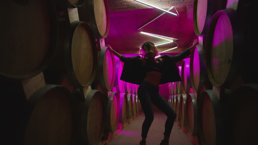 Hot girl dancing, walking . Dances with real strobe lights in colorful light winery with brandy , whiskey or wine barrels . Sexy body posing in wine house .  Clubbing scene in slow motion . | Shutterstock HD Video #1017234106