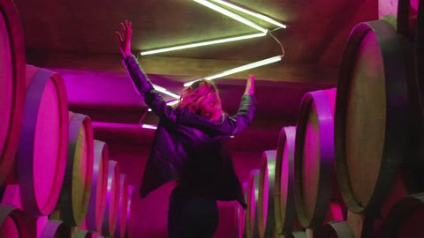 Hot girl dancing . Dances with real strobe lights in colorful light winery with brandy , whiskey or wine barrels . Sexy body posing in wine house .