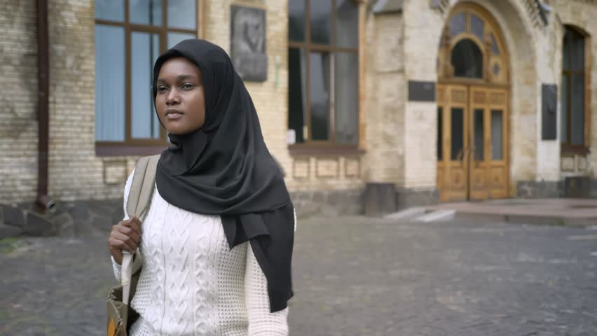 Young african american muslim woman in hijab walking in park near university and waving to someone, happy and cheerful
