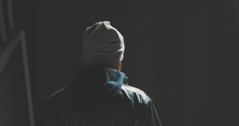 |Young man dressed in a jacket and a knitted hat walking down the dark stairs. 4k shooting with hands
