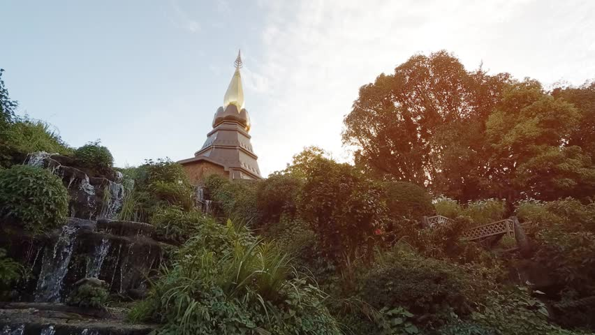 Water tumbles down a little waterfall. with the spire of a Buddhist temple in the background. at Doi Inthanon. Stock footage 4k with sound.