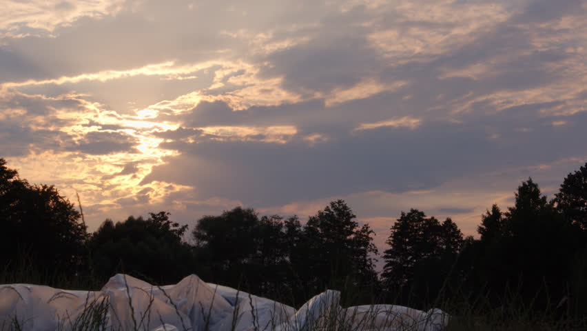 Allegory Slow Motion Shot Of A Female Rising From A Pile Of Plastic Foil Laying On The Ground In A Natural Environment At Sunset