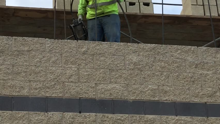 Man Consolidating Fresh Grout Placed in Masonry Wall with Vibrator