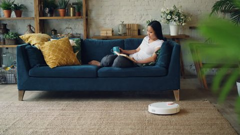 0fc04c5792 Relaxed Asian woman is reading book turning pages sitting on couch at home  when robotic hoover