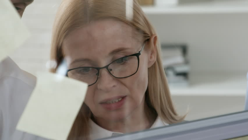 Close-up of blonde senior businesswoman in eyeglasses standing behind glass wall in the office and discussing ideas on adhesive notes with colleagues | Shutterstock HD Video #1017294916