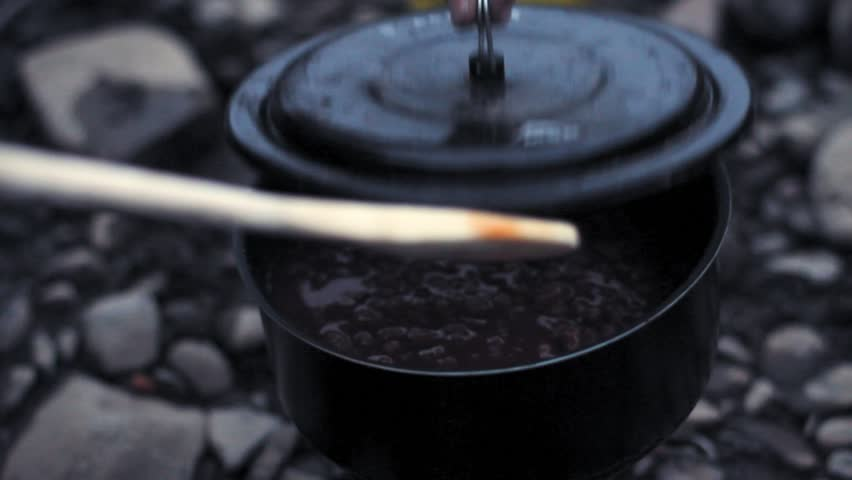 Yukon river, Yukon Territory, Alaska. Night camp of a canoe expedition to Alaska. Cookingbaked beans in a pot while hand with wooden spoon stirs.