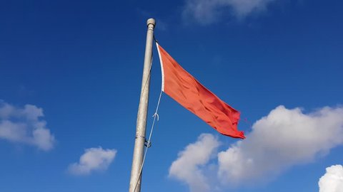 Close up of a red flag blowing in the wind with blue sky and clouds in the background.