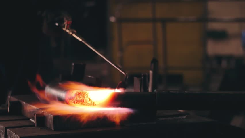 Man is heating the metal tube at the metal construction factory. Heavy industry. Workshop of metal structures