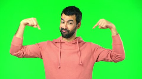 man with pink sweatshirt on green screen chroma key pointing down