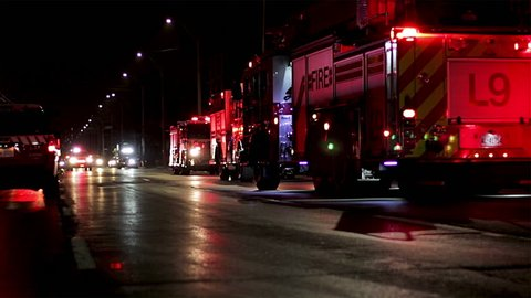 Firetrucks blocking the street off at night during an emergency building fire. Flashing lights and sirens of fire engines on a city street.