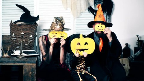 Woman in suit of witches, man in suit of sorceress and boy in suit of skeleton are hiding behind a melon against a background of scenery to a halloween. Family is having fun on Halloween