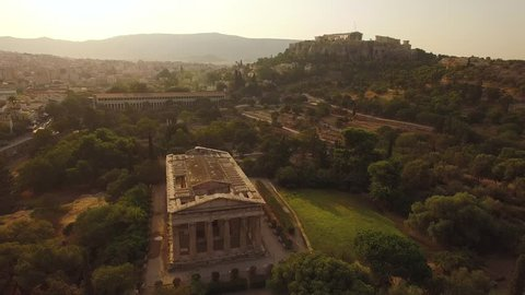 Aerial shot looking east past the Temple of Hephaestus showing the surrounding ruins and the Parthenon on the hilltop in the background during golden hour sunrise