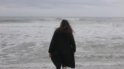 A beautiful girl runs barefoot into the cold sea, touches the water, and runs away