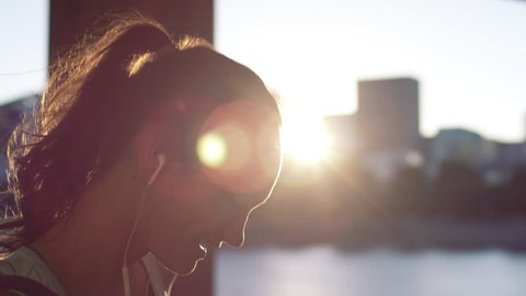 Happy Young Woman Listens To Music On Her Way To Yoga Class, In City At Sunset, Slow Motion