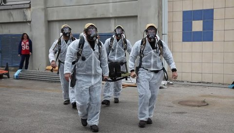 ALON HATAVOR, ISRAEL - MARCH 12, 2015:  Soldiers from Northern Israel with protective gear practice carrying an injured person during simulation drill of leak of Ammonia chemical at Tnuva Dairy