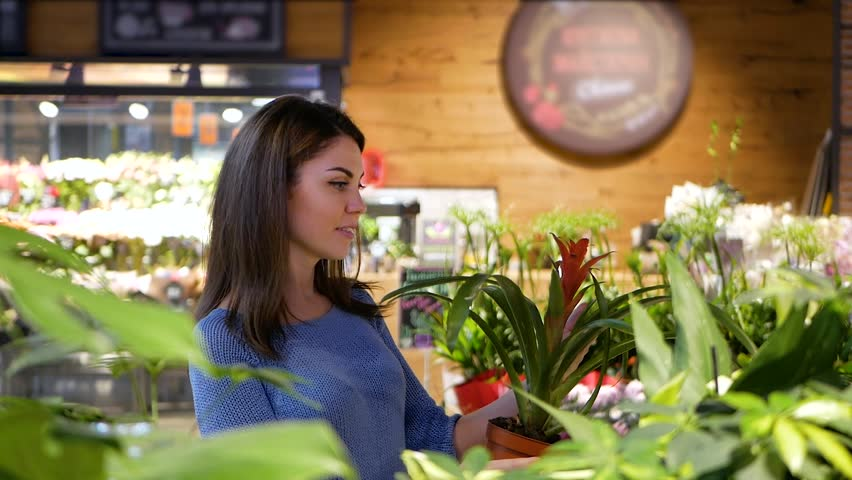 Pretty girl chooses flowers in flower shop | Shutterstock HD Video #1017478756