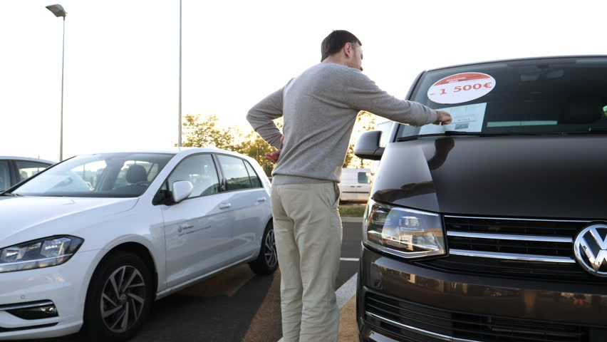LYON, FRANCE - CIRCA 2018: Curious Caucasian young customer admiring the brown Volkswagen Vw transporter van offered by Vw Das Welt car dealer - checking the price and discounts of 1500 euros