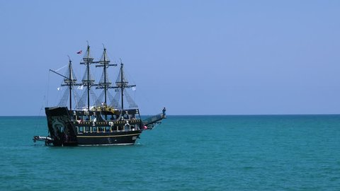 Tourists tour on old style pirate ship on calm clear blue ocean towards the horizon