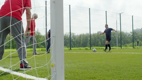 Group of four senior men playing with football outdoors on warm summer day, one of them standing at goal net and catching ball, his teammate clapping hands