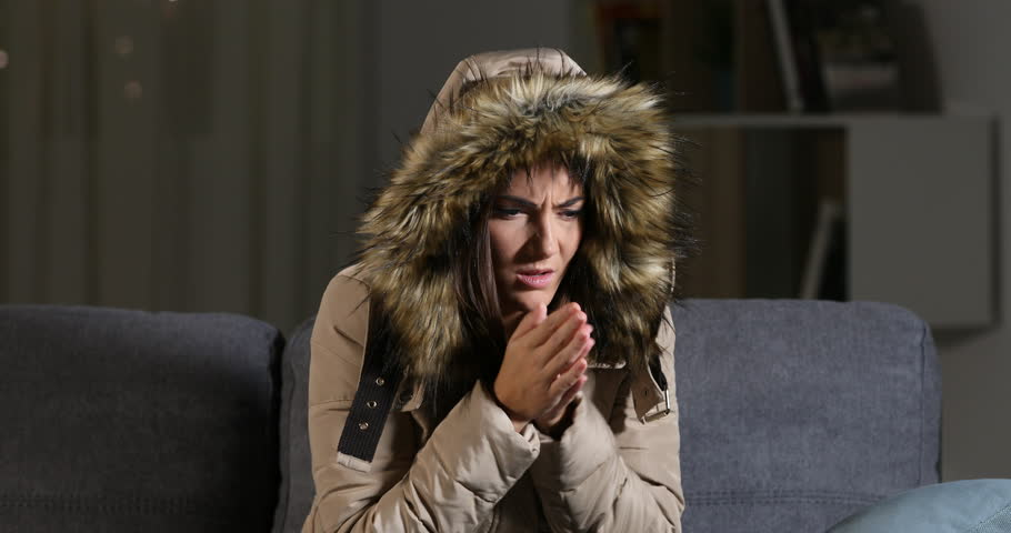 Angry woman warmly clothed complaining looking at camera in a cold home sitting on a couch | Shutterstock HD Video #1017519166