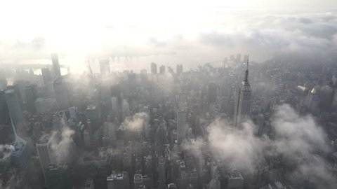 New York City Circa-2015, aerial view flying south over Midtown Manhattan at sunrise, facing the East River, with low level clouds