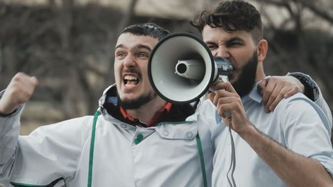 Two guys on strike shouting into a megaphone close-up. People are yelling on the street. Angry football fans in casual wear. Cool plan. Serious boys at a slow motion demonstration.
