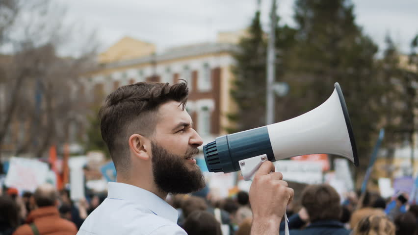 Young adult angry man goes and shouts in a megaphone on strike. Caucasian guy with a beard yelling into the loudspeaker at the rally. Office worker displeased with dismissal or reduction.