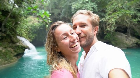 Young couple taking selfie surrounded by lush green jungle, stunning waterfalls in the background. Selfie point of view of couple travelling. Adventure lifestyle concept