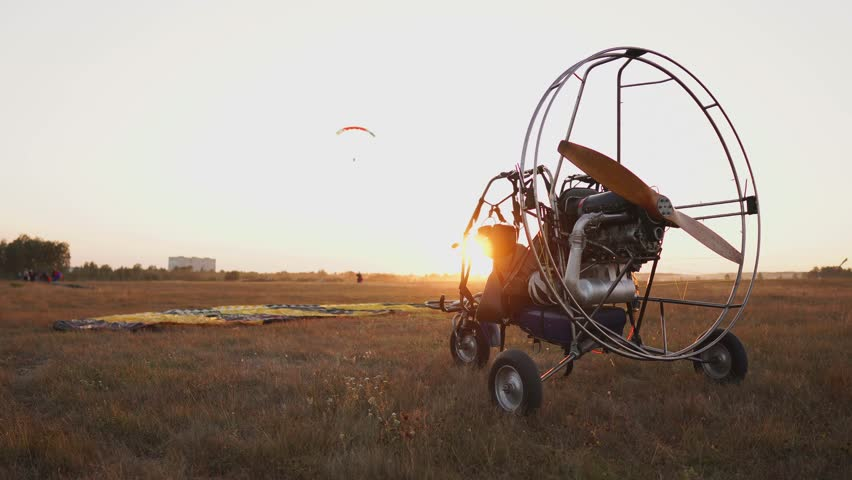 Motor paraglider stands at the airport in the rays of sunset sunlight. In the background, a parachutist lands and the camera slowly moves around the paraglider #1017545896