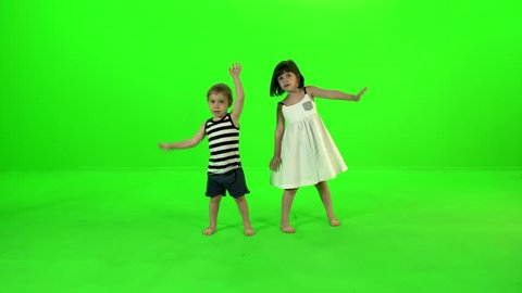 Cute little kids dance, jump, and clap their hands cheerfully over a green screen.