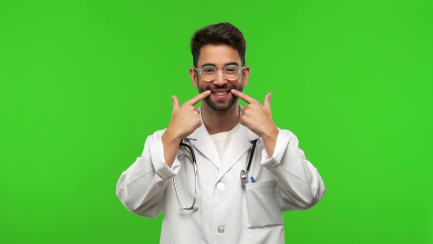 Young doctor man on green chroma smiles, pointing mouth, concept of perfect teeth, white teeth, has a cheerful and jovial attitude | Shutterstock HD Video #1017671926