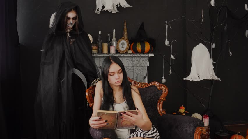 Intensive stare of spooky scary Death Reaper Skeleton on young dreamy brunette reader in Halloween fest decoration room | Shutterstock HD Video #1017674386